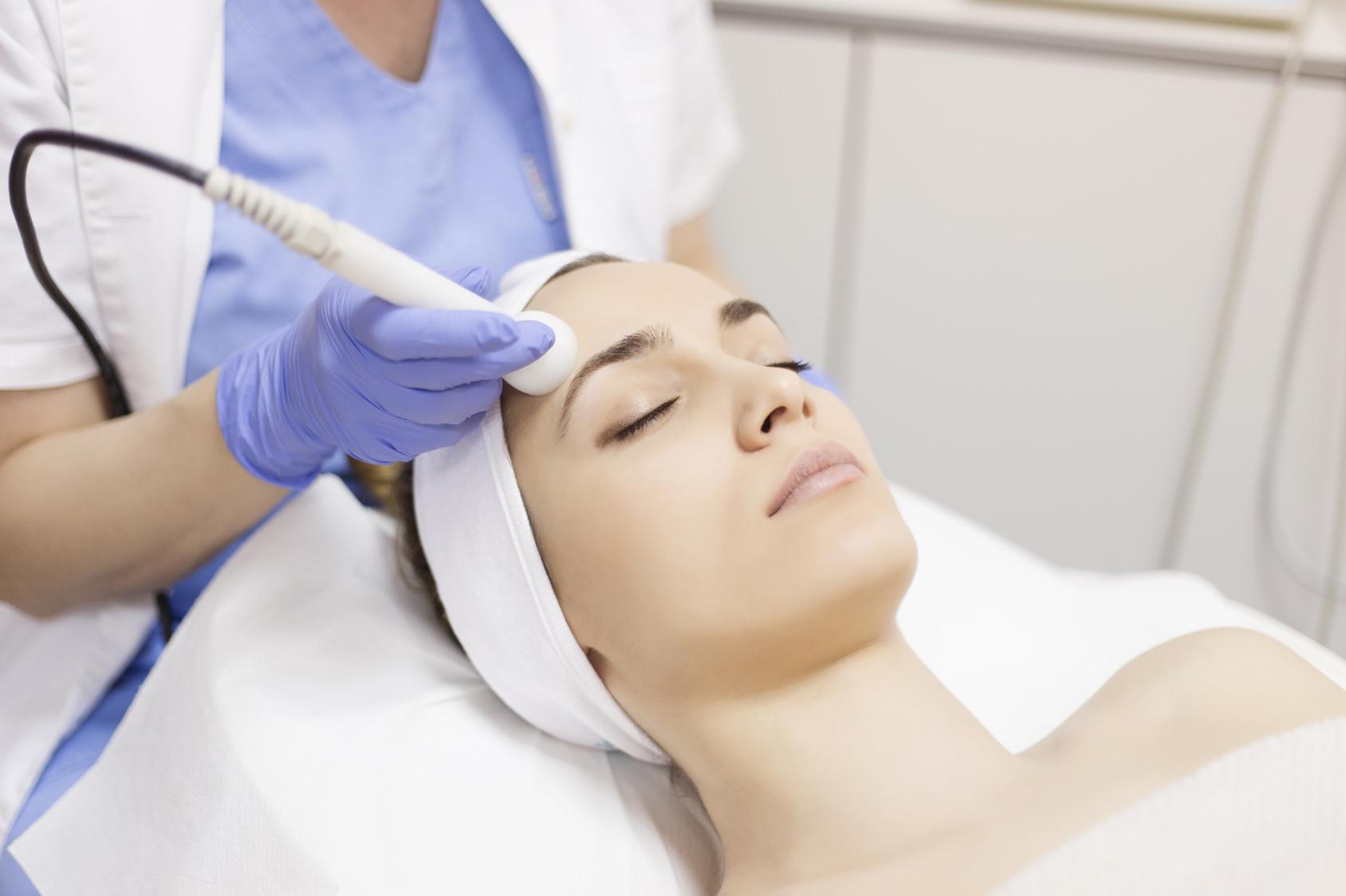 Skin care. Young woman receiving facial beauty treatment. Facial
